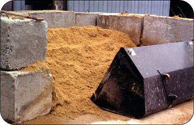 Compost bin constructed of large concrete blocks.