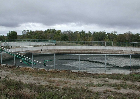 Picture of a pump agitating the liquid manure in a fenced, circular concrete storage structure.