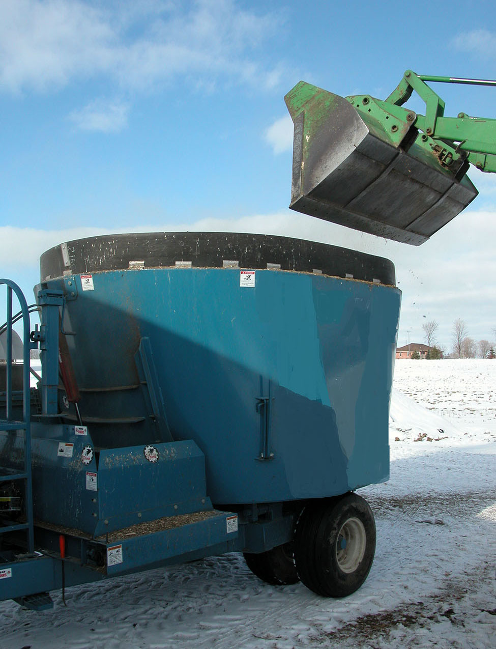 Blue vertical TMR mixer with tractor bucket dumping in feed